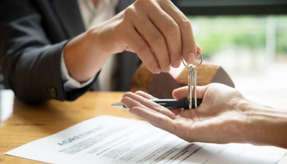 two people transferring a set of car keys in their hands, with a written agreement on the table